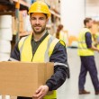 Warehouse worker smiling at camera carrying a box — Stock Photo #65558701