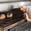 Happy baker by open oven — Stock Photo #65558801