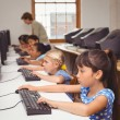 Cute pupils in computer class with teacher — Stock Photo #65558809