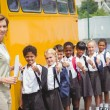 Cute schoolchildren waiting to get on school bus — Stock Photo #65559471