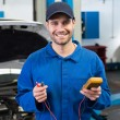 Mechanic smiling holding tool — Stock Photo #65559953