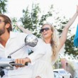 Cute couple riding a scooter — Stock Photo #65559985