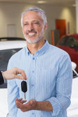 Businessman giving car key to customer — Stock Photo