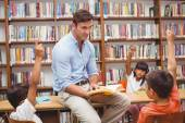 Cute pupils and teacher having class in library — Stock Photo