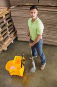 Man moping warehouse floor — Stockfoto