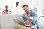 Businessman phoning and holding laptop on sofa — Stock Photo