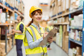 Smiling warehouse manager holding clipboard — Stockfoto