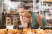 Pretty brunette looking at pastrys — Stock Photo