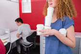 Student holding pile of coffee cup near classmate — Stock Photo
