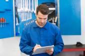 Mechanic writing on a clipboard — Stock Photo