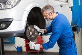 Focused mechanic adjusting the wheel — Stockfoto