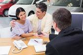Salesman giving key to smiling couple — Stock Photo