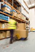 Worker pushing trolley with boxes in a blur — Stock Photo