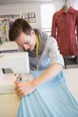 Smiling student using sewing machine — Stock Photo