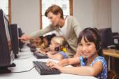 Cute pupils in computer class with teacher — Stock Photo