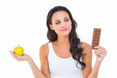 Brunette deciding between apple and chocolate — Stockfoto