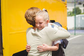 Mother hugging her daughter by school bus — Stock Photo