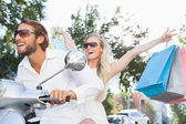 Cute couple riding a scooter — Stock Photo
