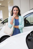 Pretty customer thinking if she buy the car — Stock Photo
