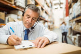 Warehouse manager writing on clipboard — Stock Photo