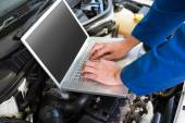 Mechanic using laptop on car — Stock Photo