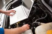 Mechanic using laptop on car — Stock Photo