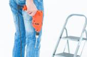 Worker holding drill in front of step ladder — Stock Photo
