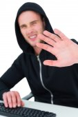 Frowning hacker gesturing and looking at camera — Stock Photo