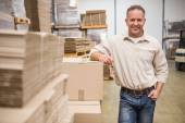 Warehouse worker leaning against boxes — Stock Photo