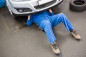 Mechanic lying and working under car — Stock Photo
