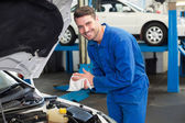 Mechanic examining under hood of car — Stock Photo
