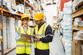 Warehouse manager talking with worker — Stock Photo