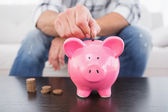 Man putting coins in piggy bank — Stock Photo