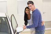 Couple holding car door handles — Stock Photo