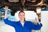 Mechanic shining torch under car — Stock Photo