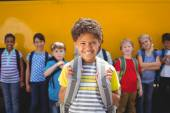 Cute pupils smiling at camera by the school bus — Stock Photo