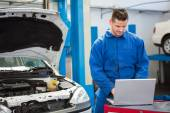 Concentrated mechanic using his laptop — Stock Photo