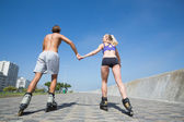 Fit couple rollerblading together on promenade — Stock Photo