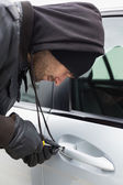 Thief breaking into car with screwdriver — Stock Photo