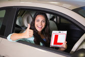 Woman gesturing thumbs up holding a learner driver sign — Stock Photo