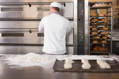Baker opening oven to put dough in — Stock Photo
