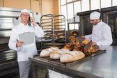 Upset baker making phone calls — Stock Photo