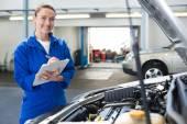 Mechanic smiling writing on clipboard — Stock Photo