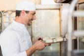 Smiling baker putting dough in oven — Stock Photo