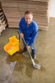 Smiling man moping warehouse floor — Stockfoto