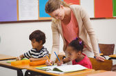 Cute pupil getting help from teacher in classroom — Stock Photo