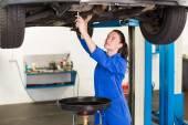 Mechanic adjusting something under car — Stock Photo