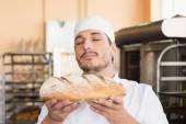 Baker smelling freshly baked loaf — Stock Photo