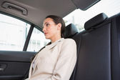 Unsmiling businesswoman sitting in the back seat — Stock Photo