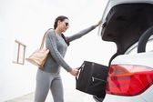 Woman pulling out a baggage of her car trunk — Stockfoto